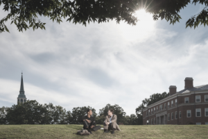 Two men sitting on a hill talking on Wake Forest campus
