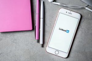 Desk with pens and phone opened to LinkedIn app