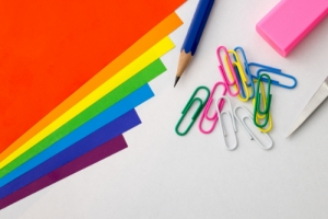 Bright colored office supplies like paper, pencil, paper clilps