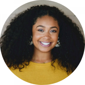 Headshot of Sydnie Williams, she is wearing a bright yellow shirt, natural hair and a big smile