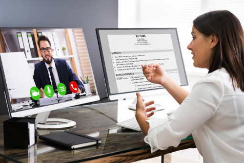Woman at a desk conducting a virtual interviewing with a male candidate on her computer screen