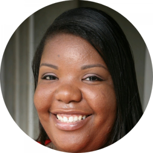 Headshot of Tiffany Newsome. She has dark hair and skin, and is wearing a smile.