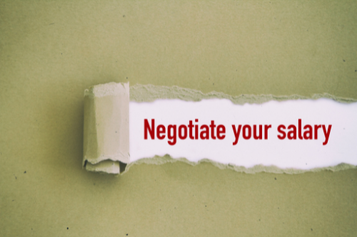 """Ripped sheet of paper with the words """"Negotiate your salary"""" in red"""