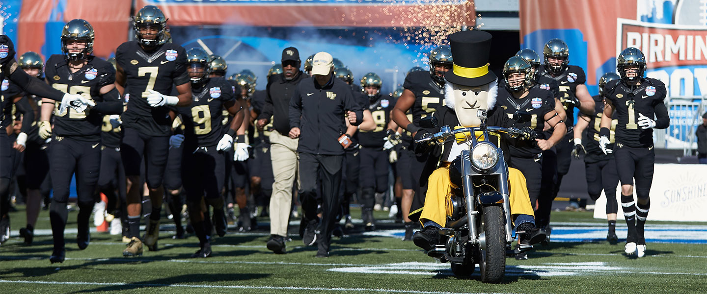 The Wake Forest Demon Deacons mascot leads the team on to the field