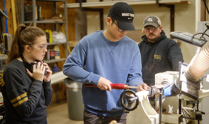 Wake Forest construction staff work with students in the wood shop in the facilities management area. The students are taking classes in multimedia storytelling and social entrepreneurship.