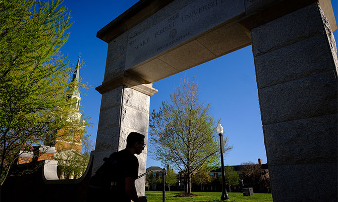 A student heads to class through the arch onto Hearn Plaza, on the campus of Wake Forest University