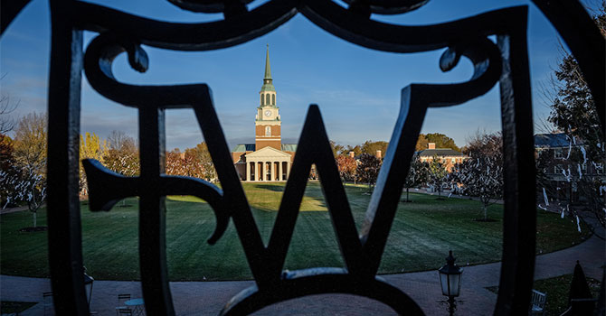 Ironwork with the WF logo frames Wait Chapelon the campus of Wake Forest University