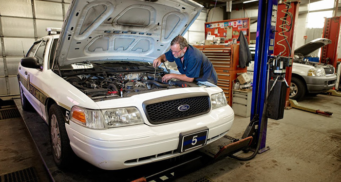 Mark, one of the fleet services mechanics, works on the engine of a campus police vehicle