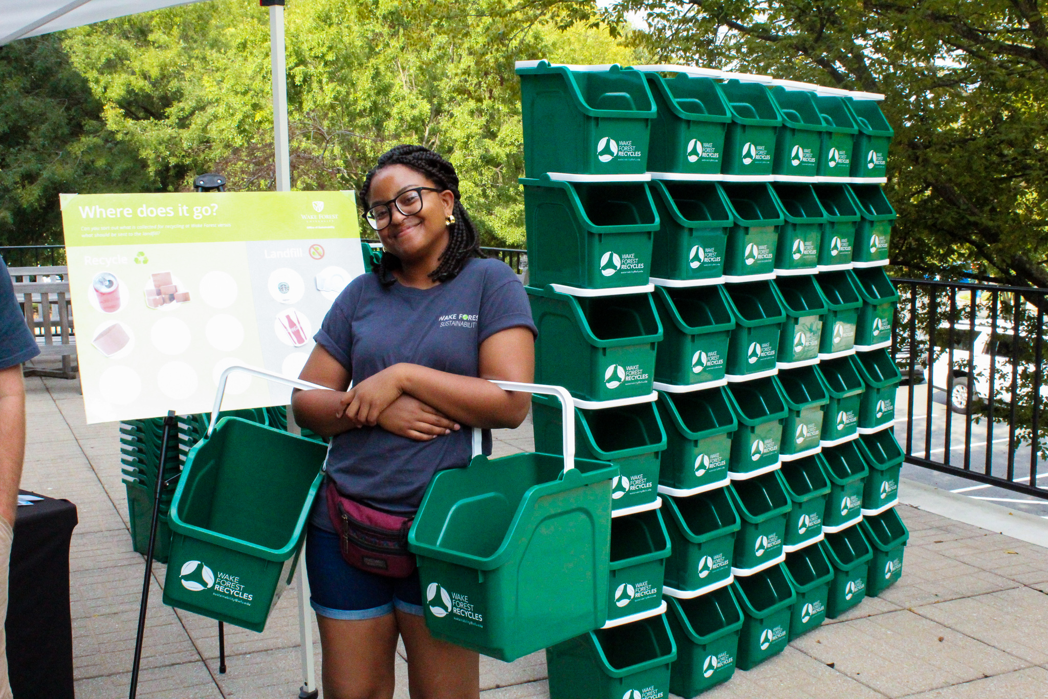 recycling bins and a woman smiling