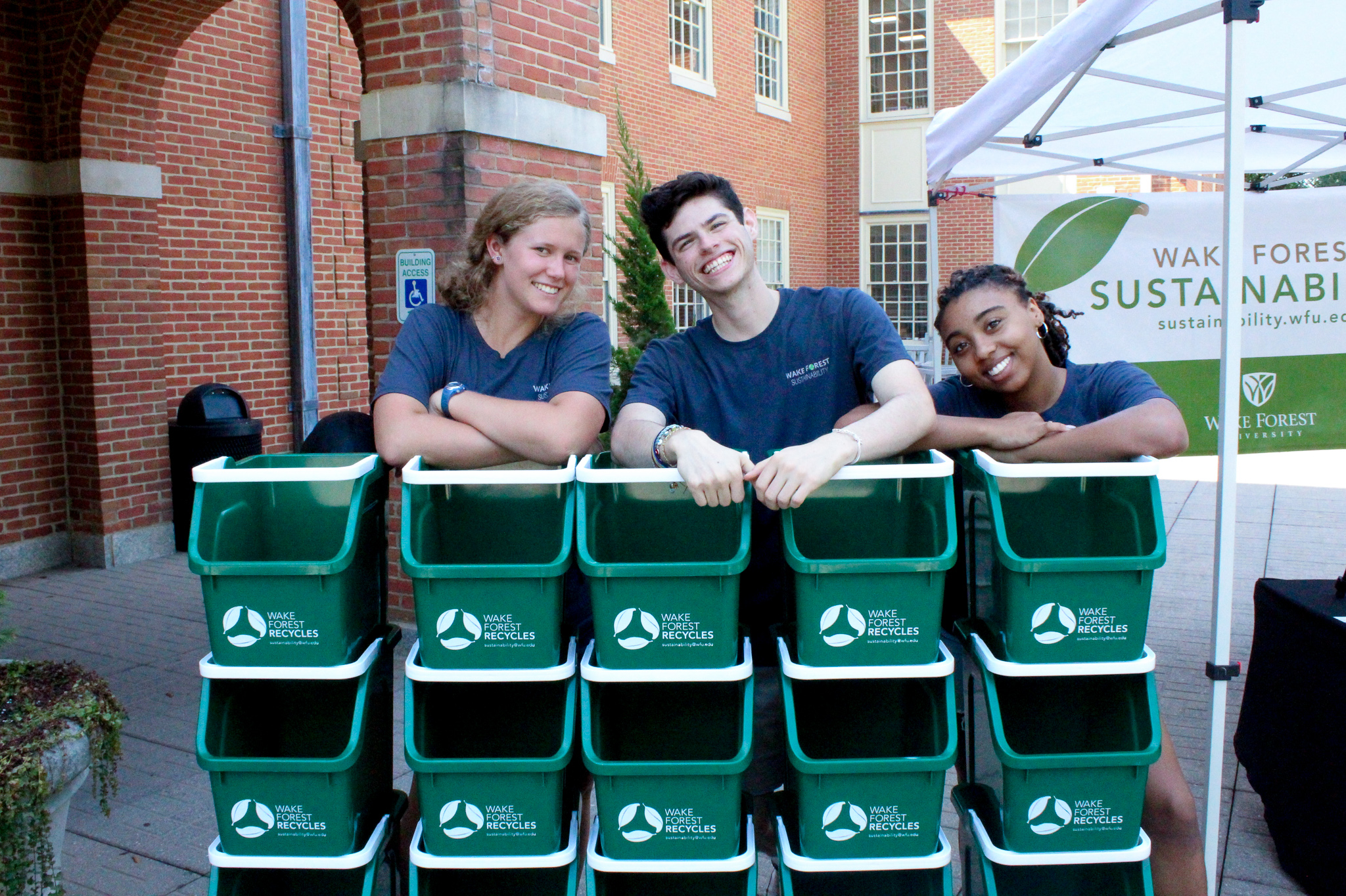 three students smiling at the stack of recycling bins
