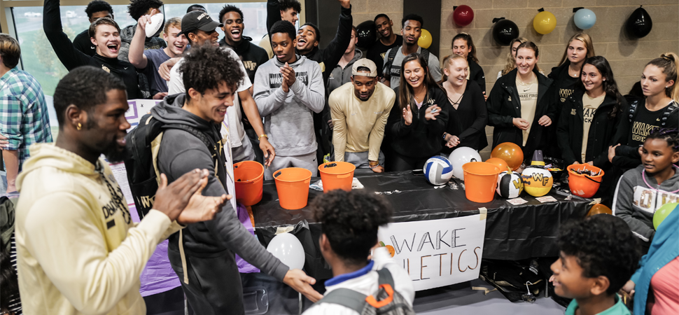 Students at the Wake Forest Athletic's Booth cheers on child after successfully completing a task at the 2019 Project Pumpkin event.