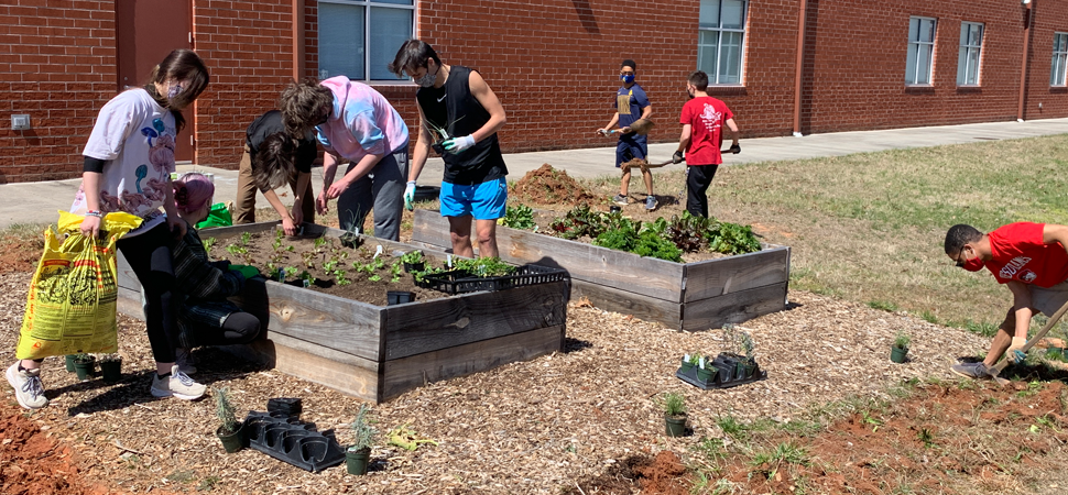 Students at Atkins High School help tend to the Childers Memorial Garden.