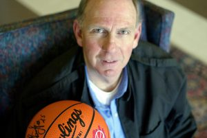 Richard Carmichael posing with a signed basketball.