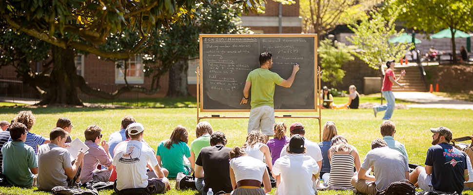 Teacher at blackboard with students in lawn