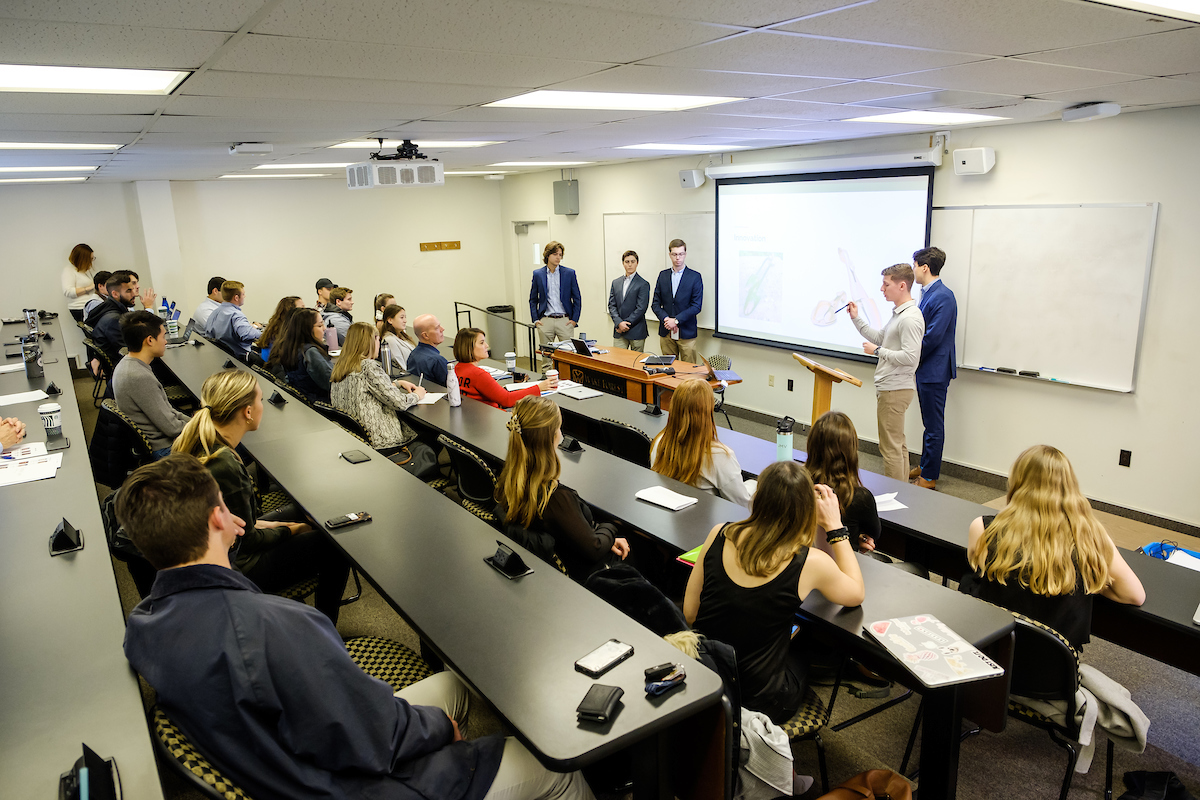 Teams of students in Dan Cohen's entrepreneurship class give their final presentations to Formé founder Maureen Stockton.