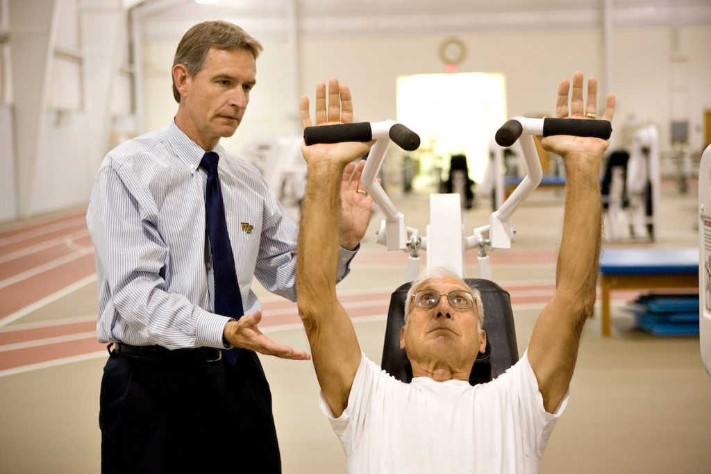Professor Jim Ross watches over a patient as the patient raises a workout bar over his head.