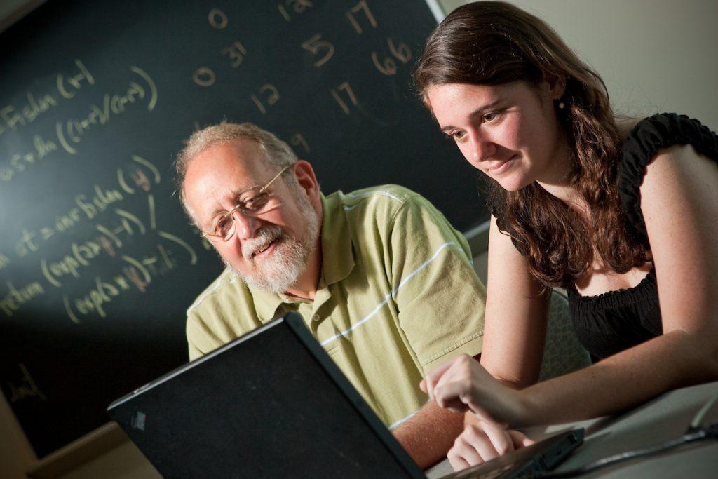 David John looks at a computer with student Rachel Black
