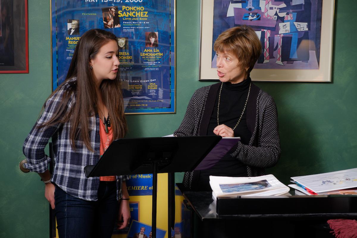 Teresa Radomski points to a piece of music on a stand next to student Katherine Sebastian.