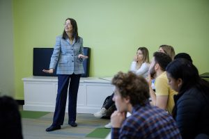 Professor Darlene May stands to the left as her students on the right look at a whiteboard off screen.