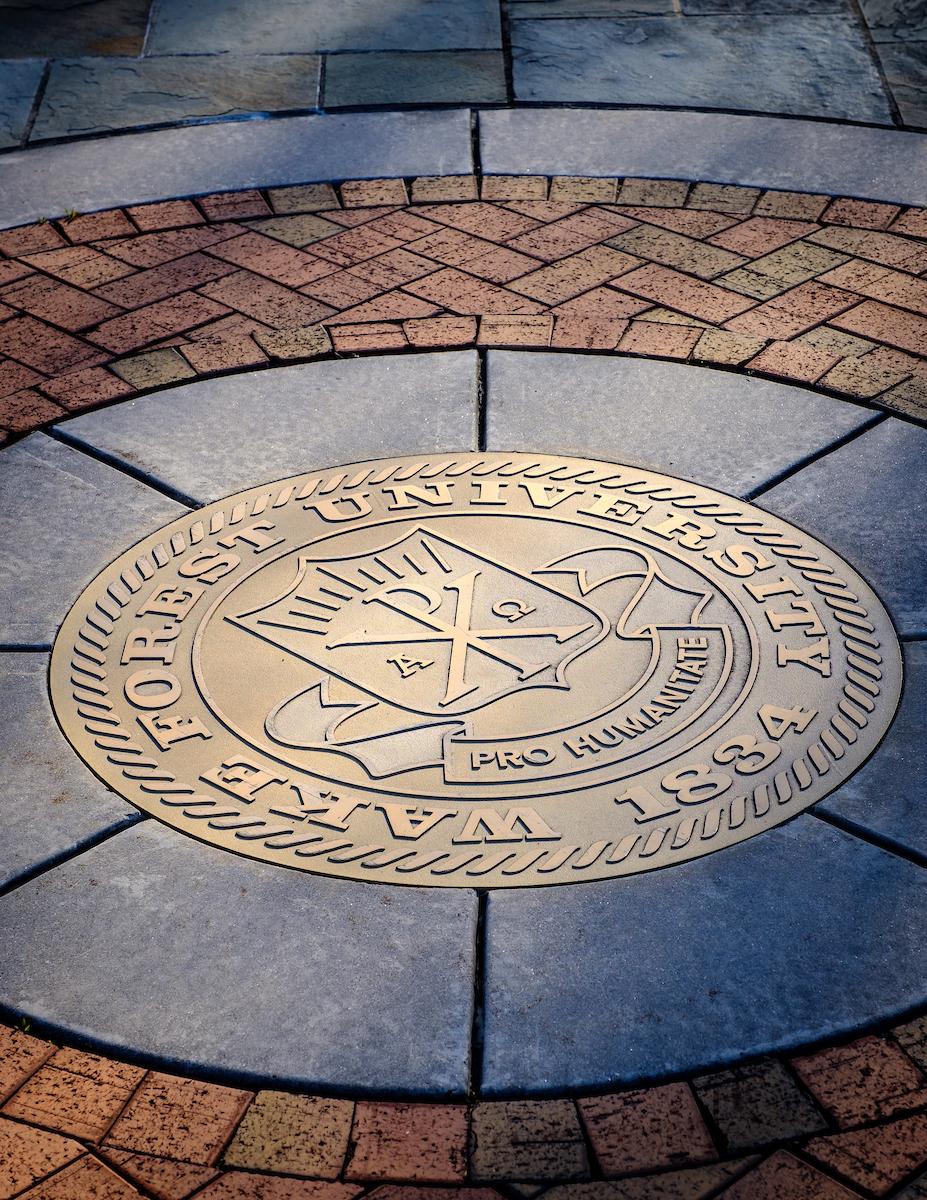 Gold university seal embedded in brick walkway