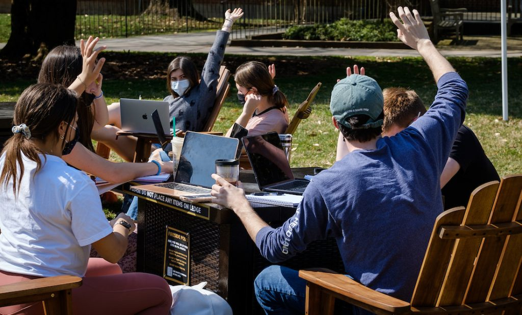 Students sit in adirondack chairs and raise their hands during an outdoor calculus class.