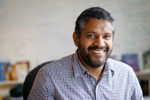 Eranda Jayawickreme sits at his desk