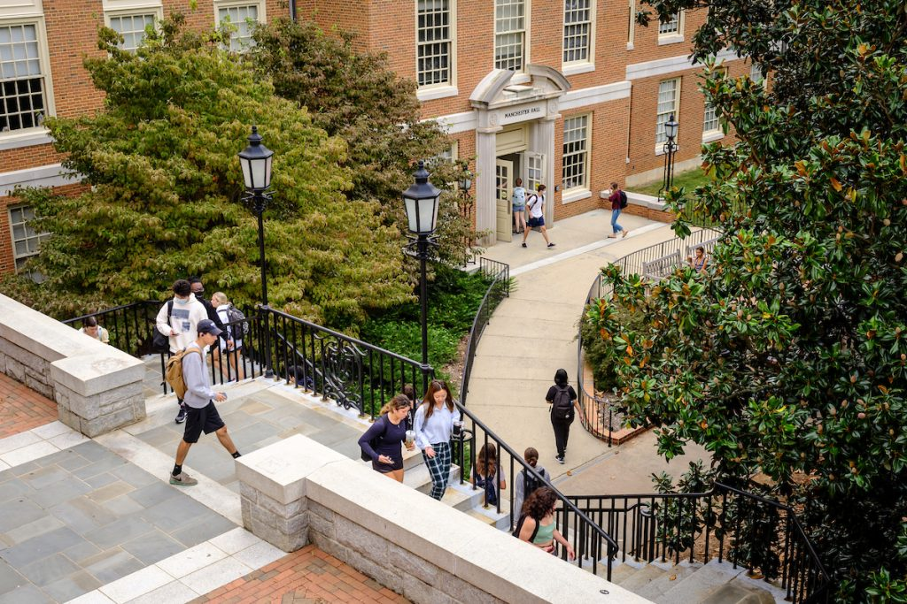 Wake Forest students walk to class on Manchester Plaza in front of Manchester Hall