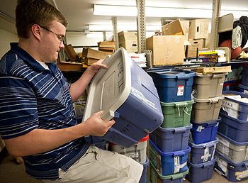 Andrew McCarty ('12) rearranges boxes of evidence in the debate storage room.