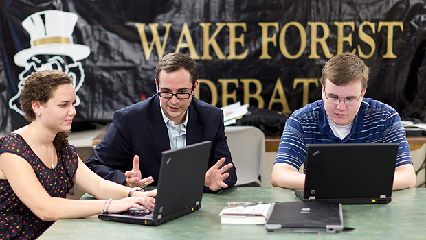 Debate coach Jarrod Atchison (center) works with debaters Alexis Shklar ('14, left) and Andrew McCarty ('12) in the debate squad room in Carswell Hall.