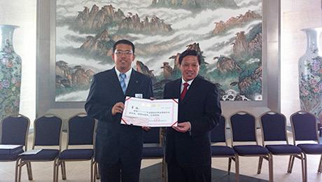 Chinese Ambassador Zhang Yesui (right) presents the award to Yuan Li.