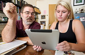 Biology Senior Lecturer Dan Johnson demonstrates the utility of an iPad as an interactive textbook to student Rebecca Perry.