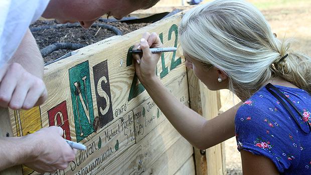 LENS participant Jordan Sullivan colors in letter on sign.