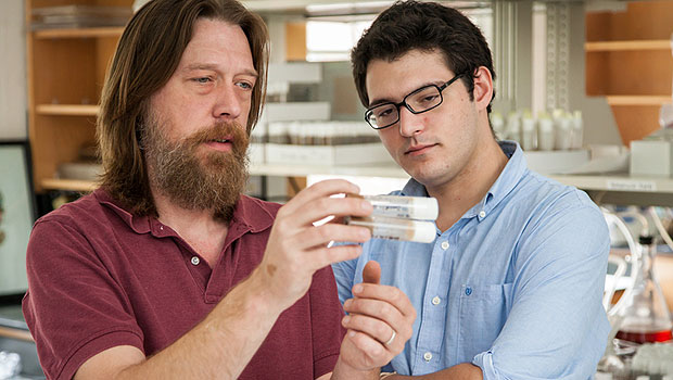 Erik Johnson examines test tubes with graduate student Jason Braco.