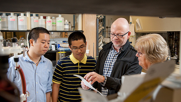 Wake Forest chemistry professor Uli Bierbach talks with staff member Linda Tuttle along with graduate students Xin Qiao (left) and Song Ding.