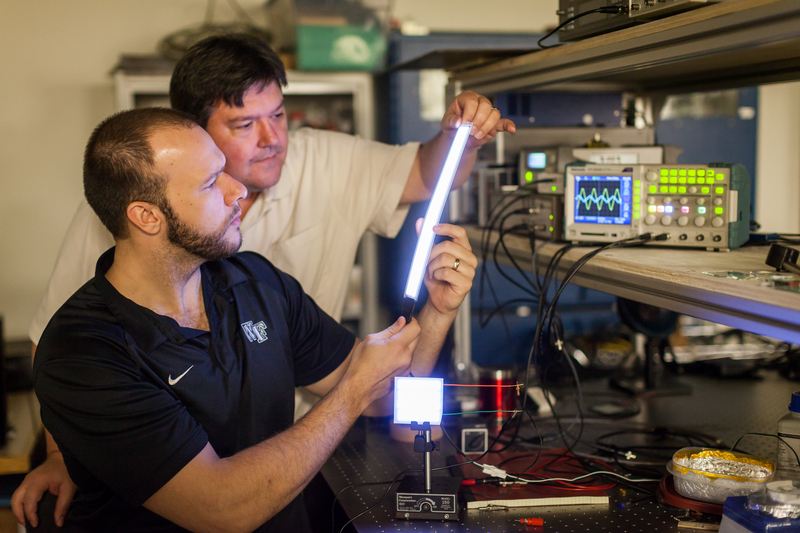 Wake Forest University physics professor David Carroll works with graduate student Greg Smith on new FIPEL lighting technology.