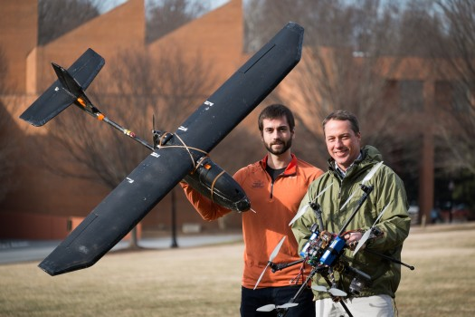 Wake Forest biology graduate student Max Messinger ('13) and biology professor Miles Silman pose with their remote controlled helicopter and fixed-wing aircraft.