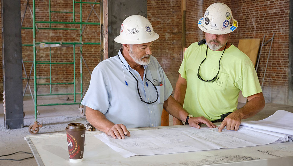 Jim Parham (left), superintendent on the Reynolds Gym transformation project, looks at blueprints.