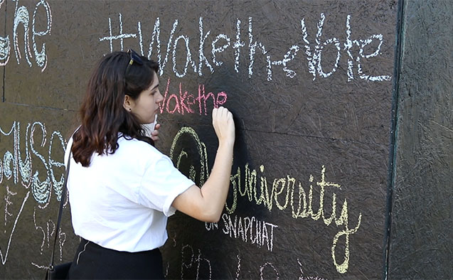 A student writes on a structure for Wake the Vote