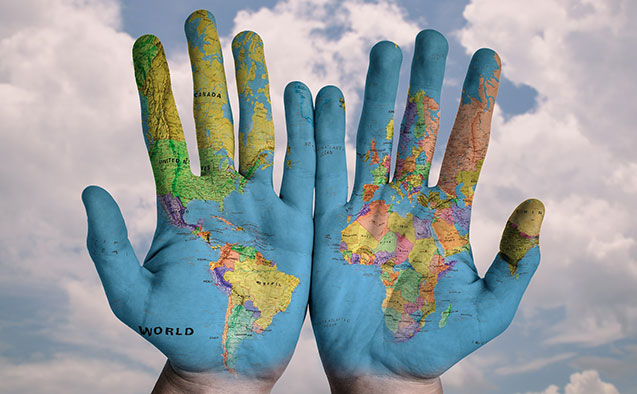 An image of hands with a map of the world painted on them