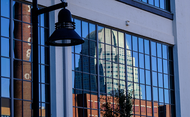 The Winston-Salem skyline reflected in a window of the Wake Downtown building