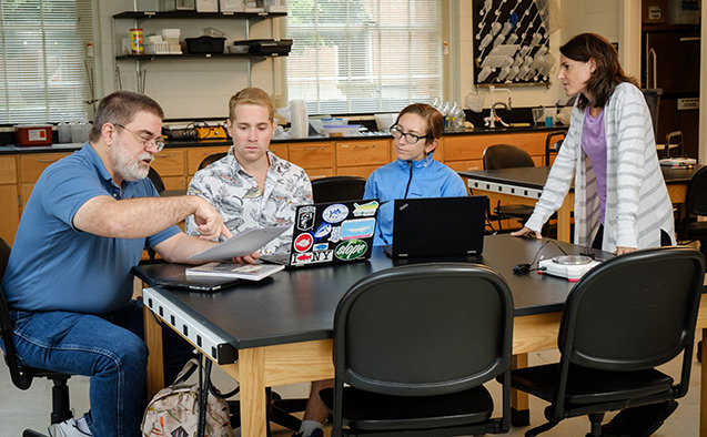 Wake Forest biology professors Dan Johnson and Sabrina Setaro talk with graduate students Noah Bressman and Jenny Howard about new methods for grading science writing, in a lab in Winston Hall.