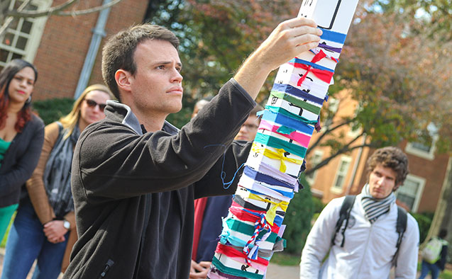 Wake Forest students participate in a prayer walk and tying torn ribbon around a peace pole following terror attacks in France.