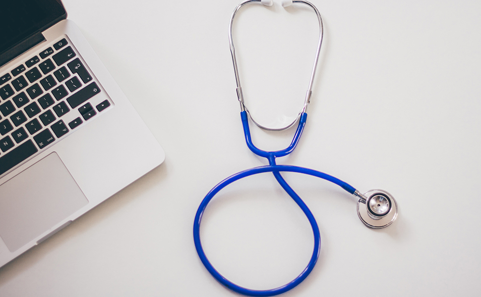 Stock image of a stethoscope and laptop.