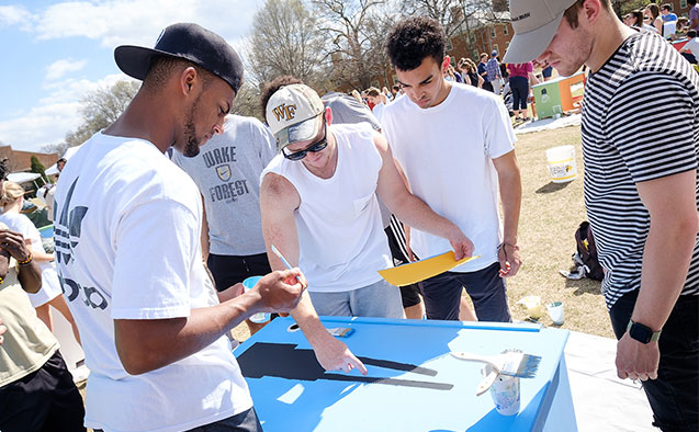 Students at WFU paint desks for students from a local elementary school