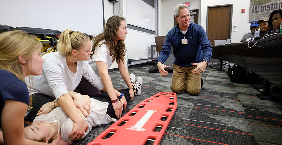 Wake Forest engineering students learn how to use a backboard for spinal injuries, one of several topics they will study this semester in hopes of improving care and outcomes, at Wake Downtown.