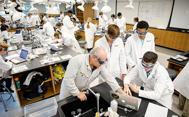 Professor Al Rives works with students on a general chemistry lab procedure.