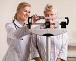 Doctor weighing senior woman - Stock image