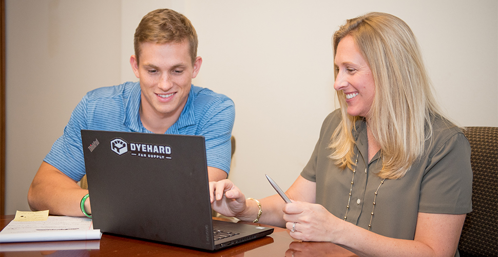 Economics major and defensive back Keegan Good works with Senior Financial Analyst Carrie Stankwytch at Dyehard Fan Supply. (Photo: McNoldy Photo)