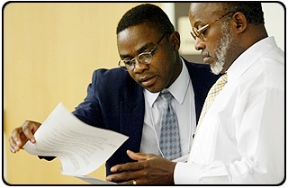 Sylvain Boko, left, talks with sociology professor Earl Smith at a campus symposium on African development.