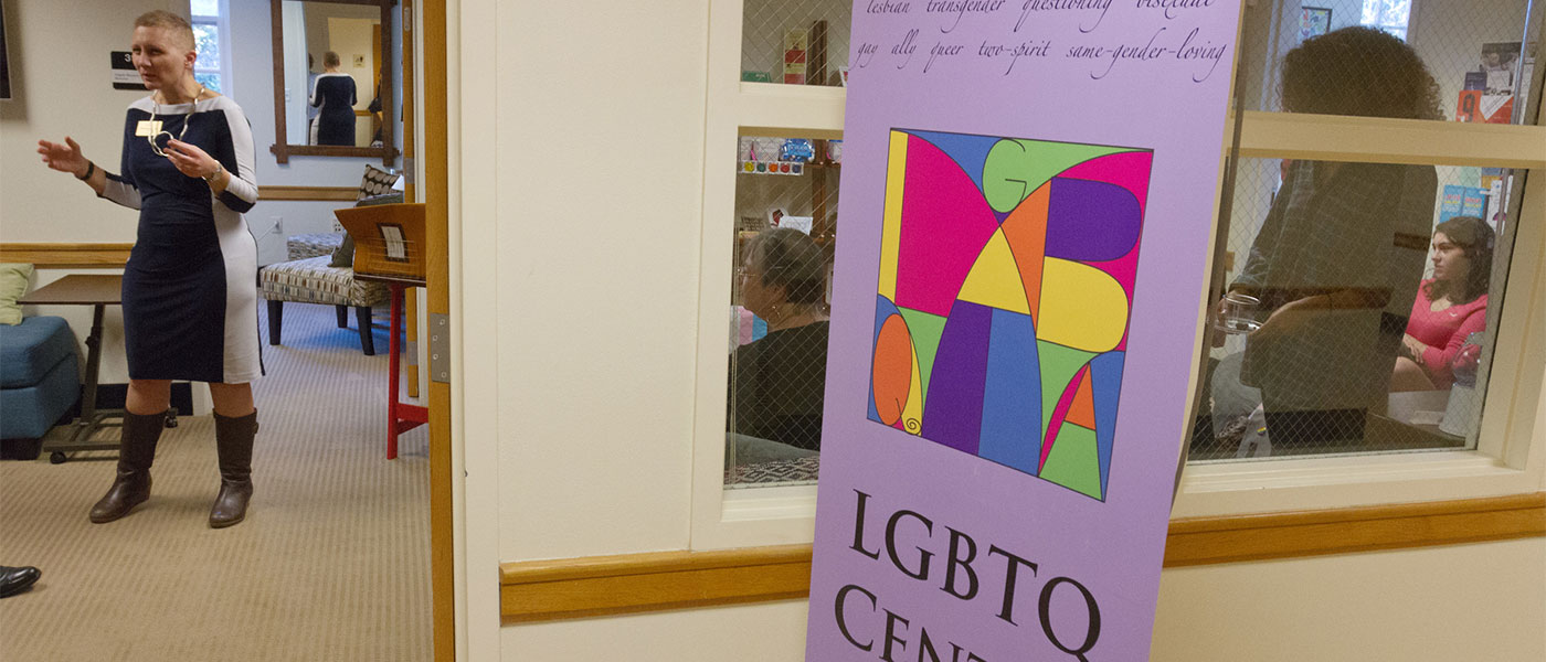Angela Mazaris, Director of the LGBQT Center, (left) shows the new center in Wake Forest's Benson University to people attending a dedication ceremony.